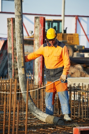 compacting: builder worker standing near trailer-mounted boom concrete pump on metal rods reinforcement of concrete casting formwork