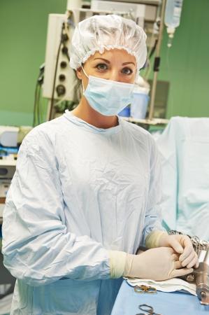 surgical: Enfermera de cirugía en uniforme realizar pruebas durante la operación de un paciente en la clínica cardiaca