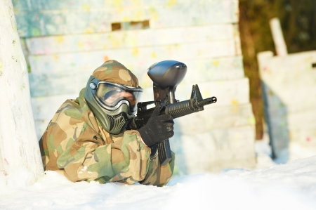 22224341: paintball extreme sport player wearing protective mask and comouflage clothing with marker gun at winter outdoors