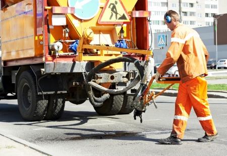 blacktopping: Road worker at asphalt roadway street patching reaparing work Stock Photo