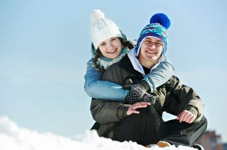 snowbank: Smiling young couple in warm clothing on snow at winter outdoors Stock Photo