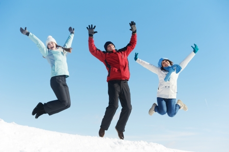 Group of young people jumping on snow at winter outdoors photo