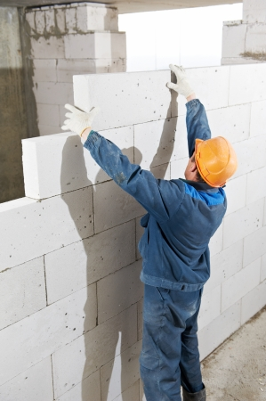 construction worker bricklayer builder installing lime sand brick during indoor wall creation photo