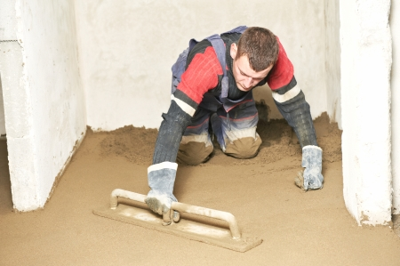 Plasterer at indoor concrete cement floor topping with float Stock Photo - 22224357