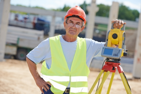 exact position: Portrait of builder worker with theodolite transit equipment at construction site outdoors during surveyor work