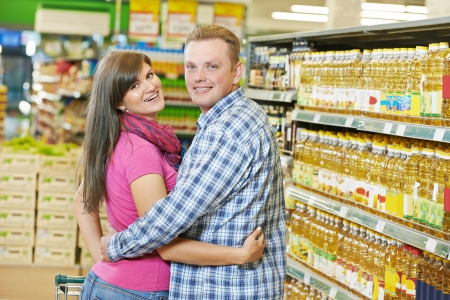 Young family couple in grocery supermarket during weekly shopping photo