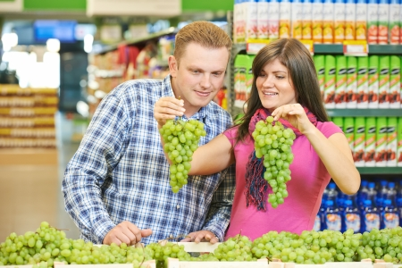 Young family couple choosing bio food grape fruit in vegetable supermarket during weekly shopping photo