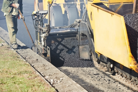 urban road: asphalt paver machine during urban road construction and repairing works Stock Photo