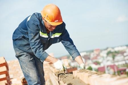 야외에서 흙 퍼티 나이프와 붉은 벽돌을 설치하는 건설 메이슨 작업자 벽돌공