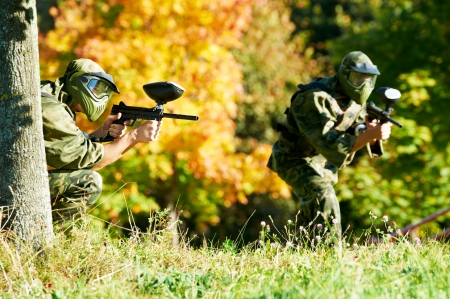 paintball: Two paintball sport players in prootective uniform and mask aiming and shoting with gun outdoors