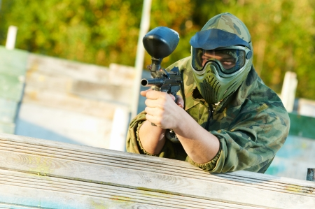 paintball sport player in protective uniform and mask aiming gun before shooting in summer photo