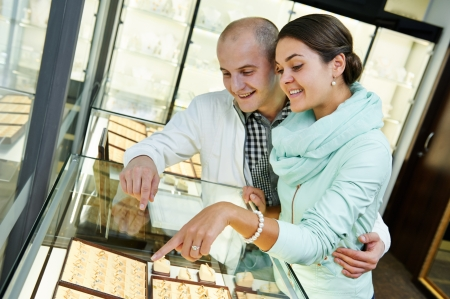 jewelry store: Young happy couple together selecting gift at jewelry boutique shop