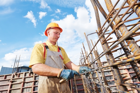 reinforcement: builder worker knitting metal rods bars into framework reinforcement for concrete pouring at construction site Stock Photo