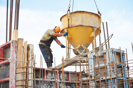 building workers at construction site doing concrete works with barrel Stock Photo - 22801523