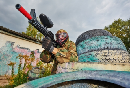 paintball: paintball player in protective uniform and mask aiming gun before shooting in summer