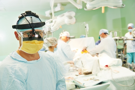 cardiosurgery: Portrait of surgeon medic in front of surgeons perfoming operation on a patient at cardiac surgery clinic