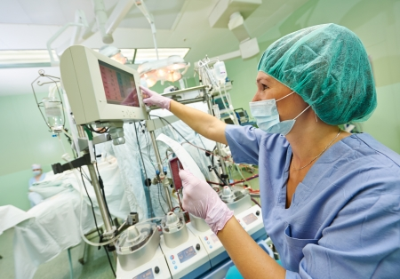 Surgery assistant nurse working with artificial cardiac valve at operation in cardiology clinic photo