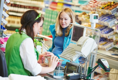 saleswoman: Customer buying food at supermarket and making check out with cashdesk worker in store Stock Photo