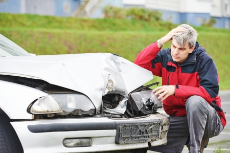 danger of accident: Adult upset driver man inspecting automobile body after crash car collision accident