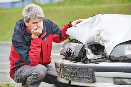 Adult upset driver man in front of automobile crash car collision accident in city photo