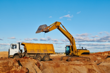 loader excavator machine loading dumper truck at sand quarry photo