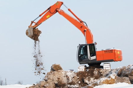 Heavy excavator loader at winter moving frozen soil works in sandpit photo