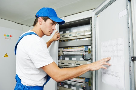 distribution box: Young adult electrician builder engineer inspecting electric counter equipment in distribution fuse box