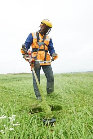 grasmaaier werknemer man het maaien van gras in groene veld Stockfoto