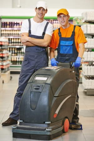 cleaning team: Workers. Floor care and cleaning services with washing machine in supermarket shop store