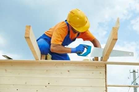 TRUSS: construction roofer carpenter worker sawing wood board with hand saw on roof installation work