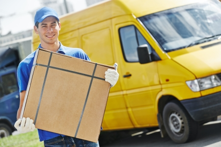 delivery package: Smiling young male postal delivery courier man in front of cargo van delivering package