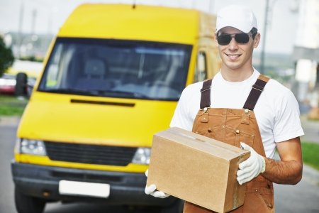 delivery courier man in front of cargo van delivering package parcel carton box photo