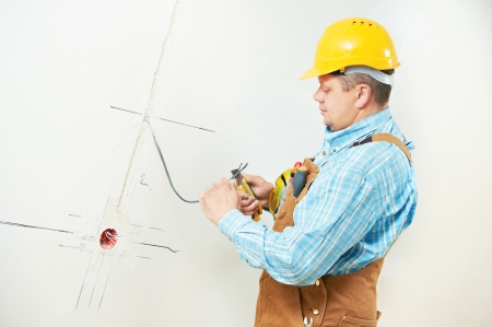enchufe de luz: Un trabajador electricista en cable cableado e instalaci�n interruptor de la luz o energ�a de la pared toma de corriente