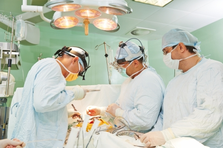 cardiosurgery: Team of surgeon in uniform perform operation on a patient at cardiac surgery clinic Stock Photo