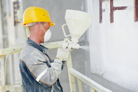 Plasterer facade builder worker with level at thermal insulation works photo