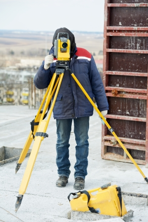 tacheometer: One surveyor worker working with theodolite transit equipment at construction site outdoors