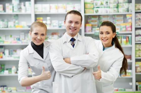 Team of cheerful pharmacist chemist standing in pharmacy drugstore