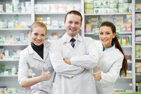 Team van vrolijke apothekerchemicus staande in apotheekdrogisterij