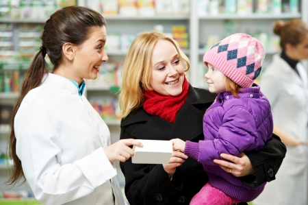 Cheerful pharmacist chemist woman demonstrating vitamins to child girl in pharmacy drugstore photo