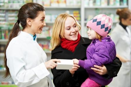 drugstore: Mujer alegre químico farmacéutico demuestra vitaminas a la muchacha infantil en droguería farmacia Foto de archivo