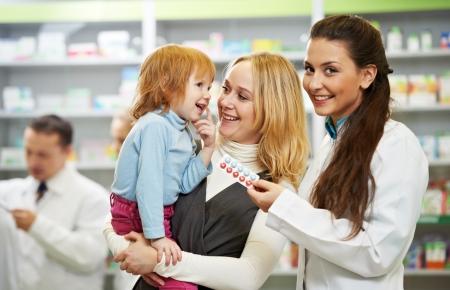 Cheerful pharmacist chemist woman demonstrating vitamins to child girl in pharmacy drugstore photo