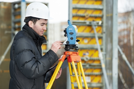 tachymeter: One surveyor worker working with theodolite transit equipment at road construction site outdoors