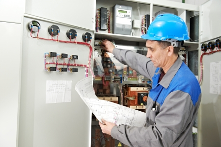 electric line: One electrician builder at work checking wire with drawing inspecting high voltage power electric line distribution fuseboard