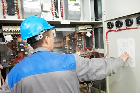electrician builder at work checking wire with drawing inspecting high voltage power electric line distribution fuseboard