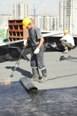 roofing system: Roofer installing Roofing felt with heating and melting of bitumen roll by torch on flame during roof repair