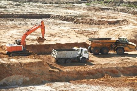 sand quarry: loader excavator machine loading dumper truck at sand quarry