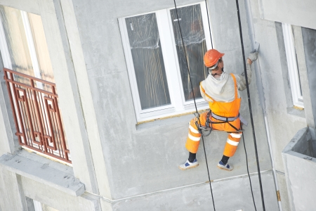 Facade plasterer at outdoor wall renovation making off joints Stock Photo