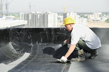 insulation: Roofer preparing part of bitumen roofing felt roll for melting by gas heater torch flame
