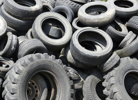 Heap of black old used automobile car tires garbage for recycling photo