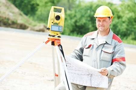 tacheometer: One surveyor worker working with theodolite transit equipment at road construction site outdoors